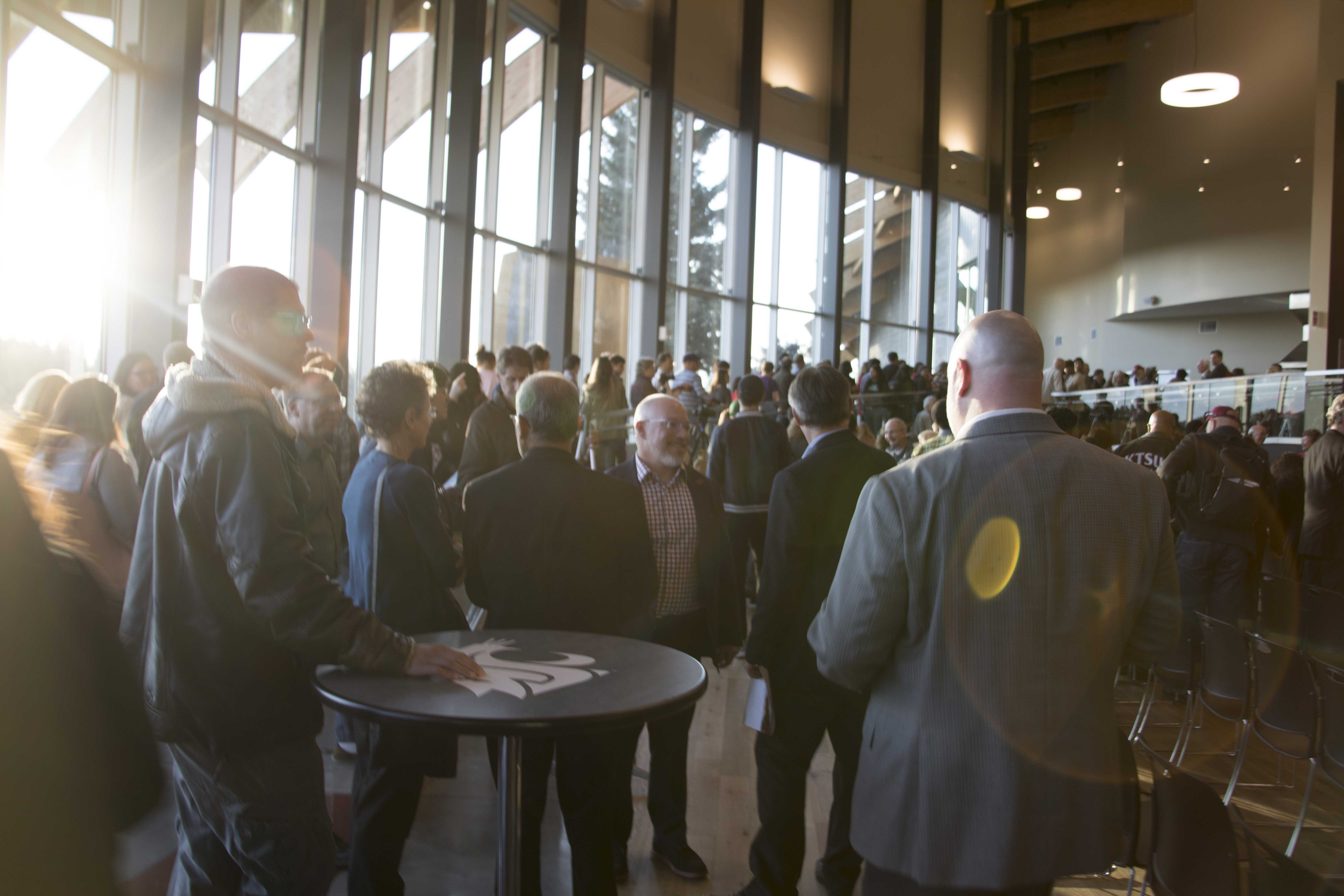 Large crowd standing during Cultural Center dedication with natural light streaming in.